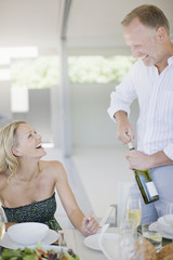 Man opening wine bottle for wife