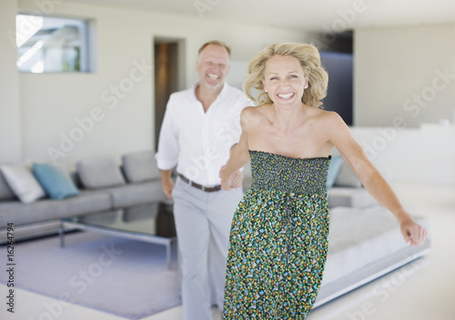 Woman pulling  husband across living room