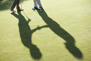 Men shaking hands on putting green