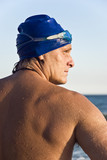 Colour portrait of a swimmer wearing blue cap and goggles.