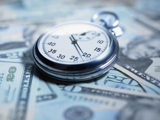 Close up of stopwatch on 20 dollar bills