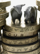 Bull and bear figurines on top of stack of pound coins