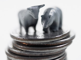 Bull and bear figurines on top of stack of quarters