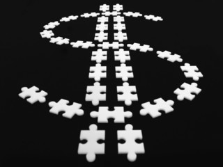 Puzzle pieces in shape of dollar sign