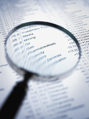 Magnifying glass enlarging list of share prices
