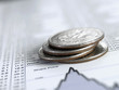Stack of quarters on list of share prices