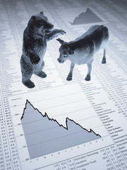 Bull and bear figurines on descending line graph and list of share prices