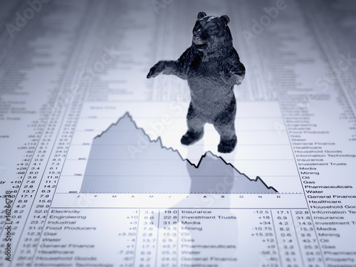 Bear figurine on descending line graph and list of share prices