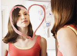 Girl looking at reflection in mirror decorated with heart-shape
