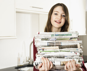 Girl carrying bundles of newspapers