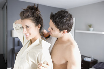 Woman fixing hair while husband watches