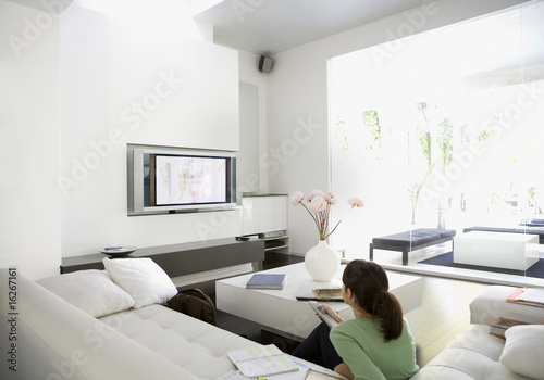 Teenage girl watching television in living room