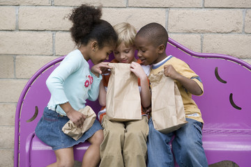 Children looking in friend?s lunch bag at recess