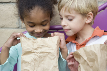 Boy looking in friend?s lunch bag at recess