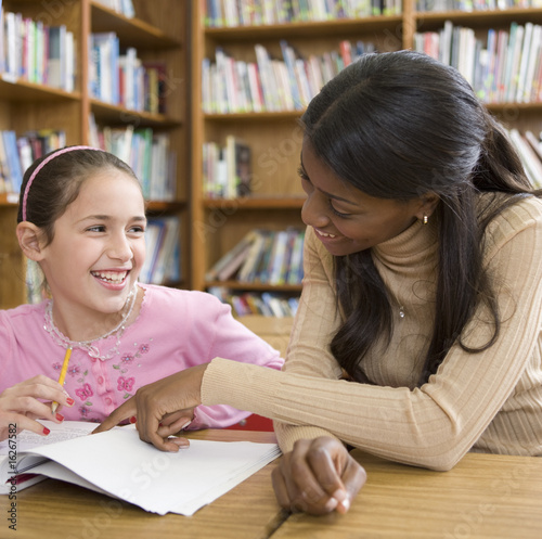 Teacher helping girl with homework