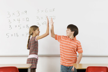 Students high-fiving after completing math at whiteboard