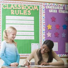 Teacher grading girl?s paper in classroom