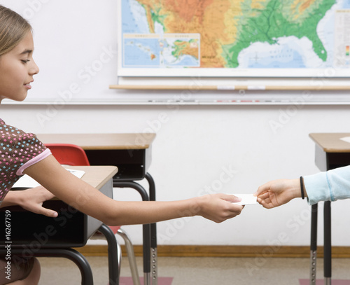 Girl passing note in classroom