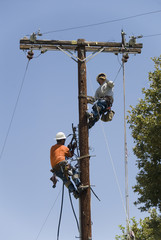 Two linemen working on pole