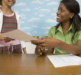 Teacher handing girl paper