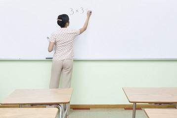 Teacher writing multiplication problem on whiteboard