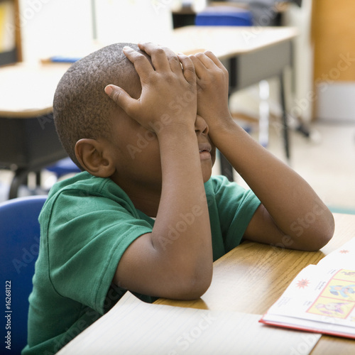 Frustrated boy rubbing eyes in classroom