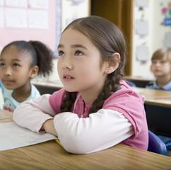 Children sitting at desks in classroom