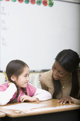 Teacher helping girl with test in classroom