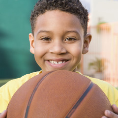Smiling boy holding basketball