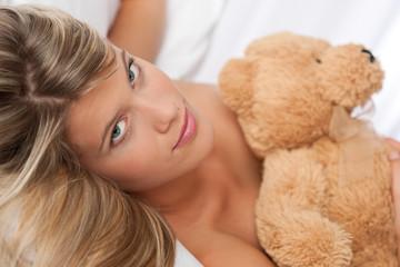 Portrait of beautiful woman holding teddy bear