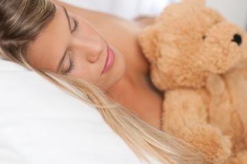 Sleeping woman holding brown teddy bear