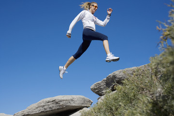 Woman running over rocks