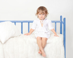 little girl sitting on the bed