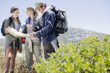 Friends hiking in remote area and looking at map
