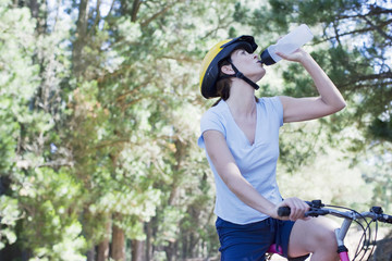 Woman on bicycle drinking water in forest