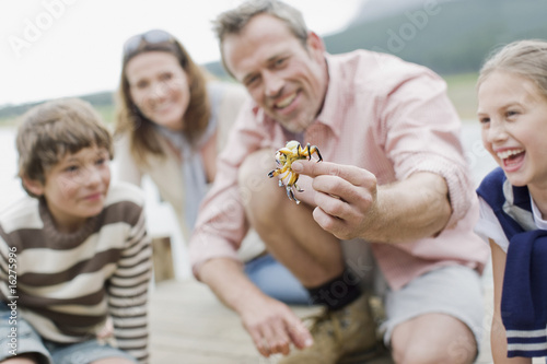 Father holding out small crab