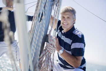 Man squatting on sailboat