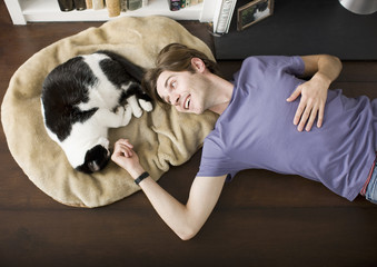 Man laying on floor with cat