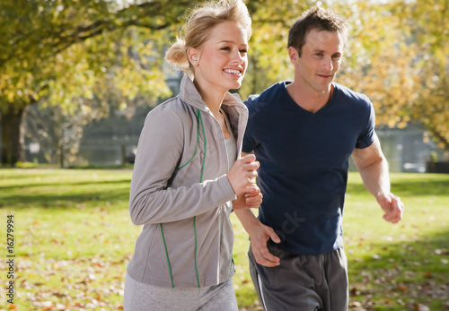 Couple jogging in park in autumn