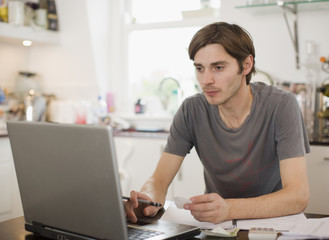 Man paying bill on laptop in kitchen
