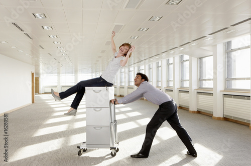 Businessman pushing co-worker on rolling stack of boxes