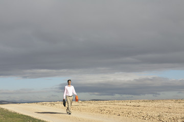 Businessman walking in remote area carrying gas can