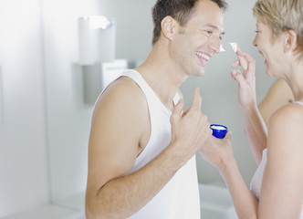 Woman putting face cream on husband?s face