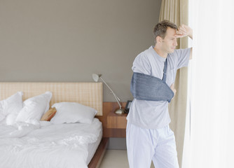 Man with broken arm looking out window