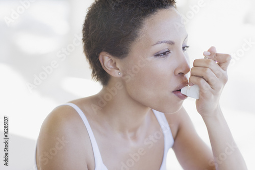 Woman with asthma using inhaler