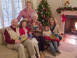 Multi-generation family holding gifts near Christmas tree