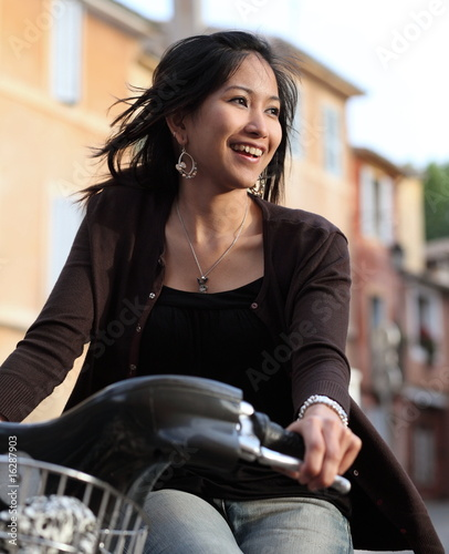 Young woman on a bike, smiling while outdoors.