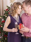 Couple holding champagne and gift near Christmas tree