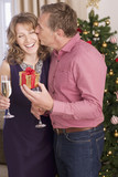 Couple kissing near Christmas tree