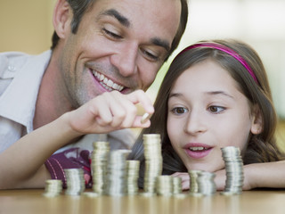 Father watching daughter stack coins